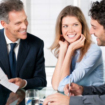 Financial consultant presenting a business investment to a smiling young couple